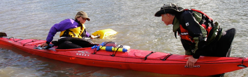 Student in red kayak being helped by instructor.