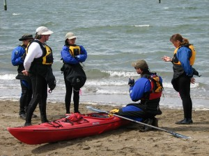 Roger Schumann and students discussing sea kayak techniques.