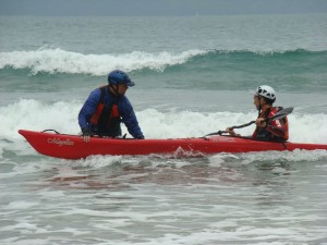 Sea kayaker learning to surf with the help of an instructor.