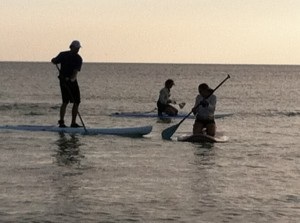 Three people Stand Up PaddleBoarding.